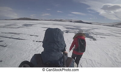 Two travelers go ice skating on a snow-covered lake.