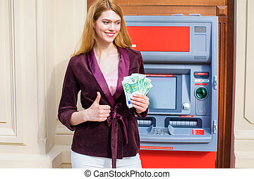 Young blonde woman is holding a cash dollars - Young...