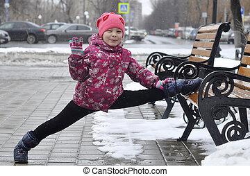 The girl shows exercise a twine on the street in the winter....