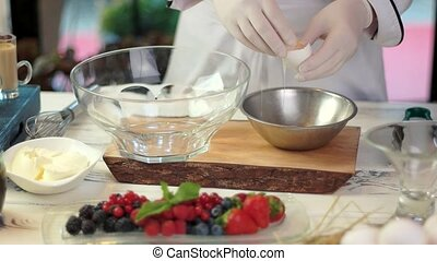 Hands separating egg yolk. Bowls on cooking table. Tips for...