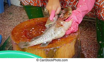 Fish Vendor Scaling a Tilapia at a Vietnamese Public Market...