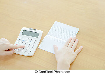 Businesswoman use calculator beside passbook