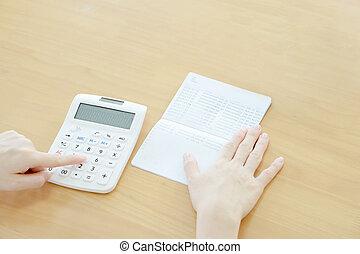 Businesswoman use calculator beside passbook