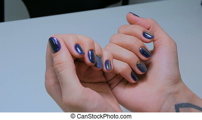 Woman shows her new manicure. Purple nail. Beauty and nail...