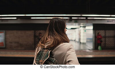 Brunette woman standing on railway station and waiting for...