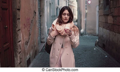 Portrait of young beautiful fashionable woman walking at city. Girl goes to work at morning and drinking coffee.