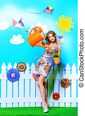 watering flowers - Summer fashion. Pretty smiling young...