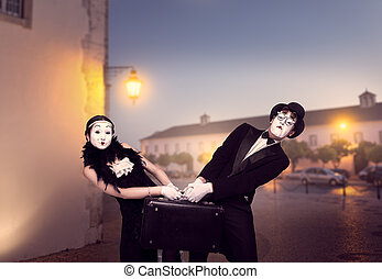 Mime actor and actress performing with suitcase. Pantomime...