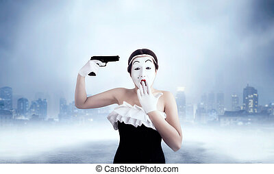 Mime female artist performing with gun. Comedian performer....