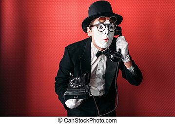 Mime theater actor performing with old telephone. Comedy...