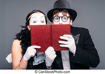 Two comedy performers posing with book. Pantomime theater...