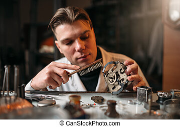 Watchmaker cleans the mechanism of old watches. Clock maker...