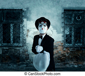 Pantomime actor in glasses shows boxer. Mime in suit, gloves...