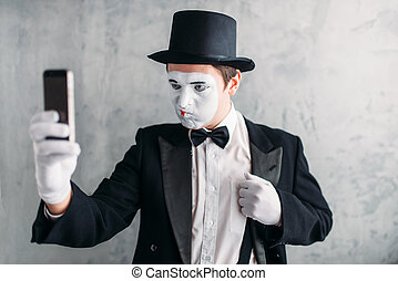 Pantomime actor with makeup mask makes selfie on camera....