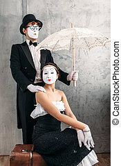 Pantomime theater performers posing with umbrella -...