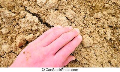 Pink skin hand looking for something in wet brown clay in...