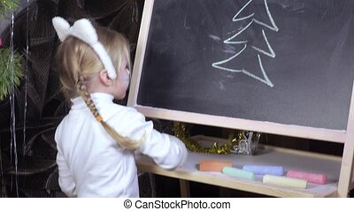 Little girl draws chalk on blackboard