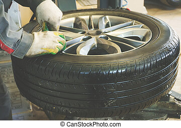 Mechanic worker makes computer wheel balancing on special...