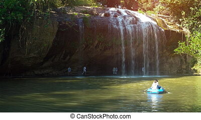 Tourists in rubber raft drift at base of Prenn Waterfall...