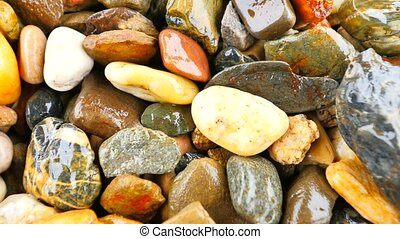 Wet stony pavement from natural pebbles.  Colorful rounded stones, traditional building material. Camera moving close up to wet ground.