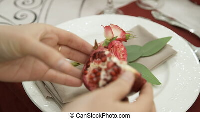 Hands florist decorate the white plate quarter red garnet....