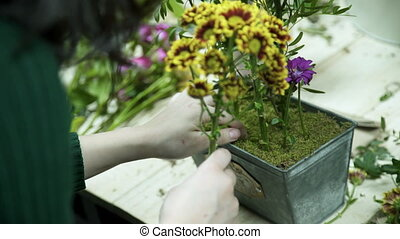 The florist inserts the stems of yellow flowers into the metal box.