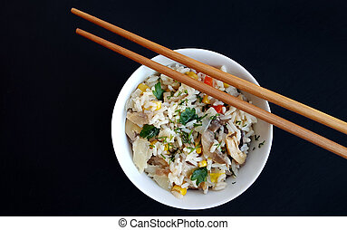 Bowl of rice with vegetables on black with chopsticks
