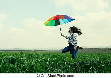 Teenage girl jumping in the green field on a background of blue sky