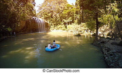 Tourists in rubber raft, drifting in natural pool at base of...