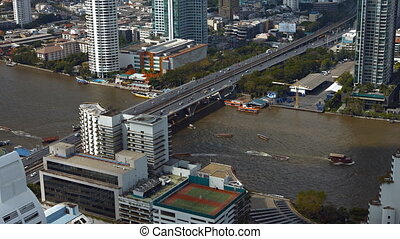 Vehicles cross bridge over Chao Phraya River as boat traffic...