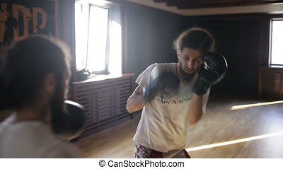 The twin brothers in boxing gloves sparring in the training...