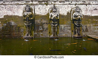 Stone sculptures of women pouring water from jars into pool....