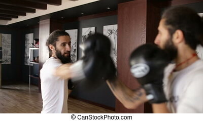 The twin brothers in boxing gloves sparring in the training hall. Chinese martial arts.