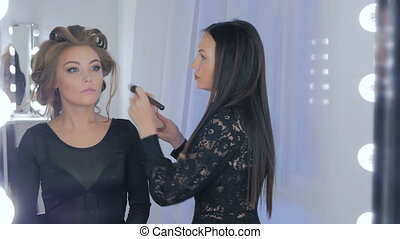 Professional make-up artist applying powder to woman face....
