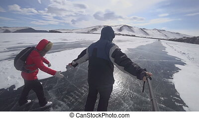 Tourists and travelers on the ice of Lake Baikal skate. Ice...