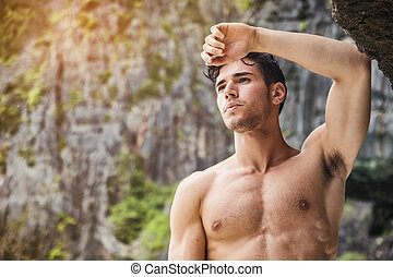 Young man standing shirtless, hills in background - Half...