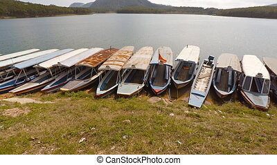 Many passenger tour boats beached in the mud in Dalat. -...
