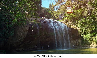 Suspended cable car gondola slowly crosses Prenn Waterfall....