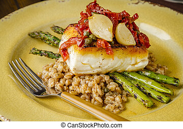 Fresh halibut filet on bed of farro - Close up of fresh...
