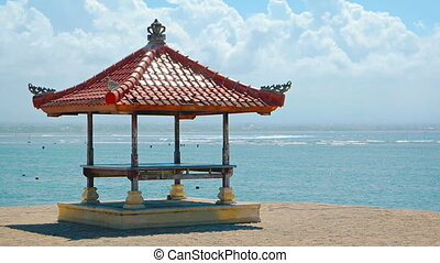 Balinese Pagoda Stands against a Tropical Sea Background -...