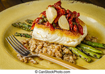 Fresh halibut filet on bed of farro - Close up of pan seared...