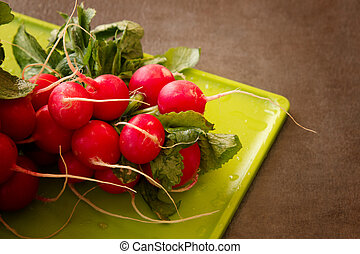 Fresh Radishes on a cutting board on a textured background -...