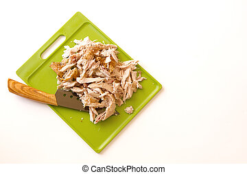 Shredded rotisserie chicken on a green cutting board and...