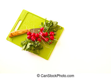 Fresh radishes on a cutting board with knife isolated on...