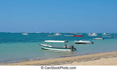 Boats and watercraft crowded along a tourist beach in Sanur,...