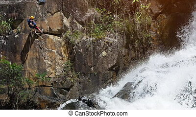 Tourist rappels down a sheer cliff beside Datanla Waterfall, with sound