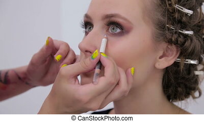 Professional make-up artist making creative make up with...