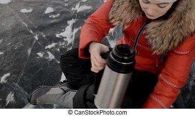 The girl is drinking tea on ice.