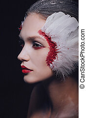 Fashion close-up portrait of a model girl in the image of a swan with a beauty amazing make-up.