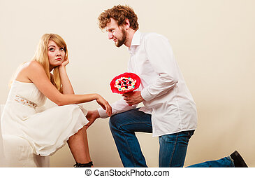 Man giving unhappy woman candy bunch flowers. - Handsome man...